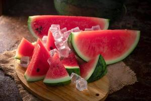 vattenmelon och vattenmelon bitar i en trä bakgrund foto