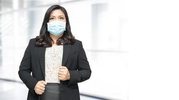 asiatisk dam som bär mask ny normal på kontoret för att skydda säkerhetsinfektion covid-19 coronavirus. foto