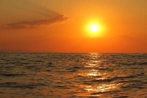 orange ljus solnedgång under havet. solreflektion på vatten naturskön, gul skymning, lugnt naturlandskap foto