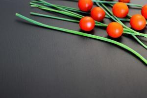 små röda körsbärstomater och färsk grön lök på rustik svart bakgrund, ovanifrån, kopieringsutrymme foto
