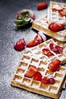 belgiska våfflor med jordgubbar och sockerpulver på svart tavlabakgrund. foto