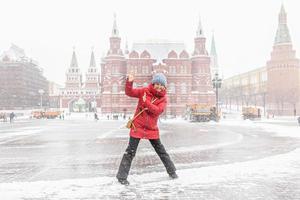 en vacker ung flicka i en röd jacka går längs manezhnaya torget i Moskva under ett snöfall och snöstorm. snöslungor arbetar i bakgrunden. foto