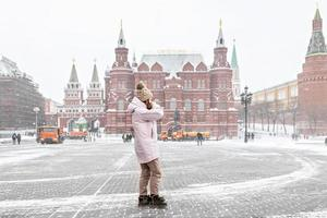 en vacker ung flicka i en rosa jacka går längs manezhnaya torget i Moskva under ett snöfall och snöstorm. snöslungor arbetar i bakgrunden. foto