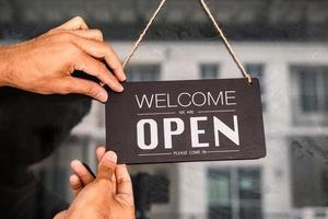 asiater med skylt öppet och stängt i restaurang för lockdown-idéer låser upp frihet turistresor för livsstilskundskylt öppet och stängt välkomnar ny normol under coronavirus sjukdom covid-19 låser upp låsning foto