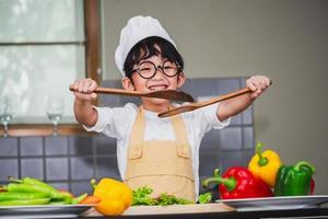 asiatisk pojke son matlagning sallad mat holdind träsked med grönsaker håller tomater och morötter, paprika på tallrik för lycklig familj laga mat njutning livsstil kök i hemmet foto
