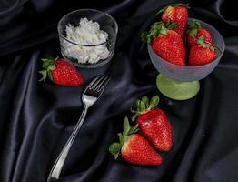 kopp mogna jordgubbar med grädde foto