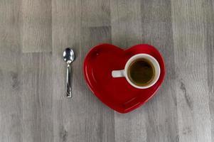 en kopp kaffe med ett hjärtformat fat foto