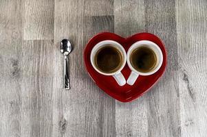 två små koppar kaffe med en hjärtfat foto