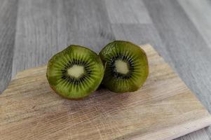 komposition med kiwi och en träskärbräda foto