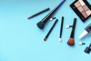 ovanifrån av dekorativ svart färg kosmetik på blå bakgrund foto