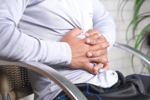 ung man som lider av magsmärta på nära håll foto