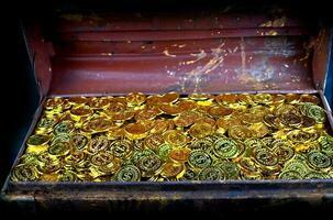 stapla guldmynt i skattkista foto