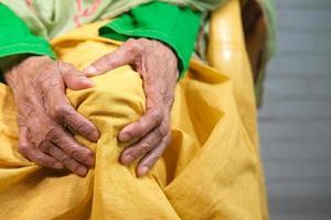 närbild på äldre kvinnor som lider av smärta i knäleden foto