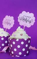 vaniljmuffins med små dekorativa hjärtan och födelsedagstecken, mot violett bakgrundsfestbakgrund foto
