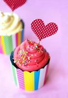 välsmakande jordgubbsmuffin med röd hjärta topperrosa bakgrund. alla hjärtans bakgrund foto