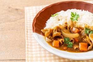 japanskt curryris med skivat fläsk, morot och lök foto