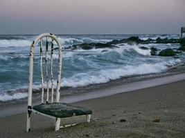 gammal stol på en öde strand. sokcho stad. Sydkorea foto