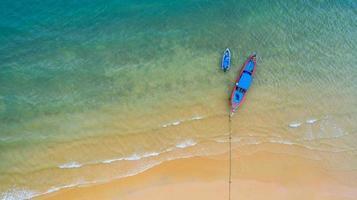 Flygfoto ovanifrån, fiskebåt, turistbåt som flyter på ett grunt klart hav, vackert ljusblått vatten i havet foto