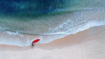 Flygfoto ovanifrån av kajakpaddling runt havet med skugga smaragdblått vatten och vågskum foto