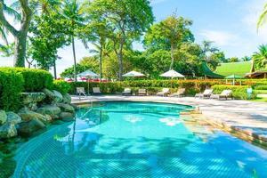vackert paraply och stol runt poolen på hotell och resort foto