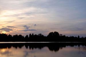 lugn sjö vid solnedgången foto