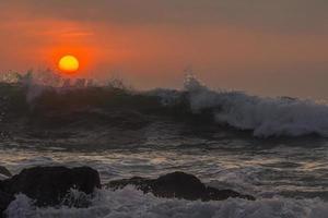 vågor som stänker i klipporna vid solnedgången foto