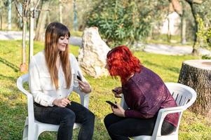 flickvänner som använder smartphone och röker cigarett foto
