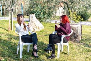 flickor dricker kaffe i trädgården foto