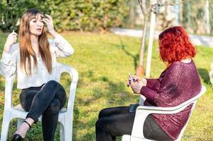 flickor röker elektronisk cigarett i trädgården foto