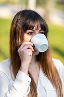 flicka som dricker en kopp te i trädgården foto