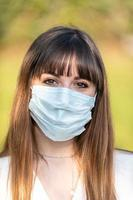 flicka som bär medicinsk mask orsakar covid 19 foto