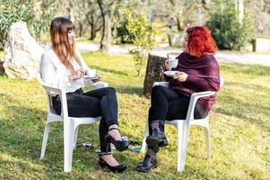 flickor dricker en kopp te i trädgården foto