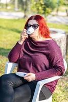 flicka som dricker kaffe i trädgården foto