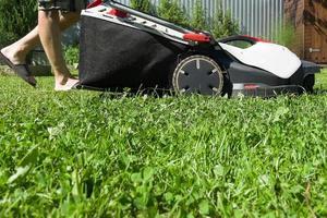 en man klipper gräset, närbild foto