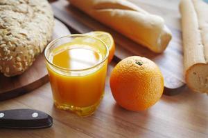 glas apelsinjuice och fullkornsbröd på bordet foto