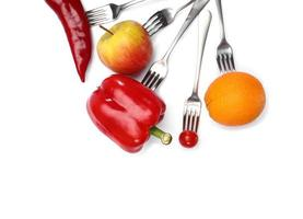 en hälsosam kost. färsk körsbärstomat, röd paprika, gurka, äpple och apelsinfrukter på gafflar på vit bakgrund. hälsosam kost och vegetarisk mat, matlagningskoncept. foto