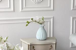 vita orkidéblommor i vas på bordet. vintage vas med orkidé hemma på byrå. foto