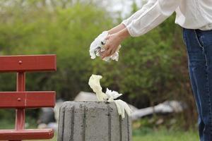 kvinnan kastar plastavfall i papperskorgen foto