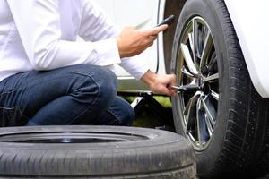 asiatisk ung man som sitter på en trasig bil som ropar på hjälp och reparerade hjulfordon på vägen och ersätter vinter- och sommardäck. säsongsbetonat däckbyte koncept foto