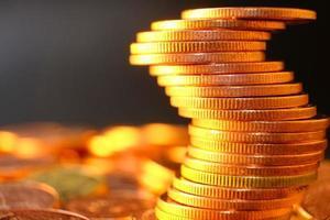 närbild gyllene mynt på bordsbakgrund och spara pengar och affärsidé tillväxt koncept, finans och investering koncept foto