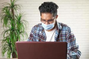 ung asiatisk man i ansiktsmask som arbetar på bärbar dator foto