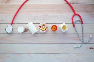 ovanifrån av medicinska pillerbehållare och stetoskop på bordet foto