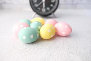 påsk koncept med ägg och en klocka på bordet foto