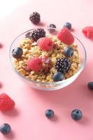 granola och bär i skål på rosa bakgrund foto
