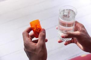 hand som håller pillerbehållare och glas vatten foto