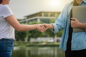 två personer skakar hand vänskap utomhus, koncept handskakning foto