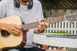 pojke som spelar gitarr hemma foto