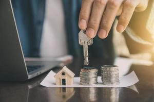 man som ger nyckelhuset till kunden, affärsinvestering fastighetskoncept foto