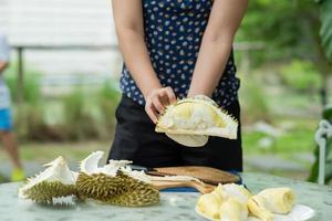 närbild kvinna hand skalar durian, kung av frukt foto
