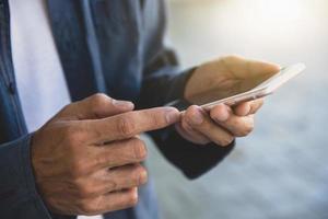 man använder smartphone-teknik. affärsman som håller mobiltelefonen foto